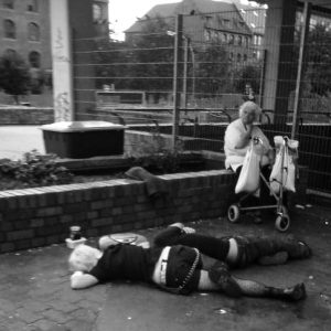 Punks sleeping while grandma waits for the bus.