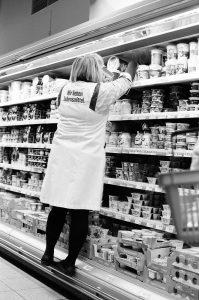 Supermarket saleswoman stands on pole on shelf