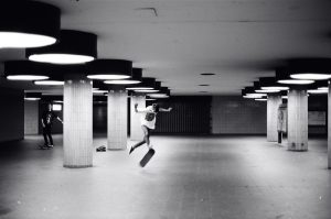 Skater does kick flip in the fair north ICC underpass