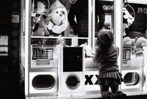 Little girl at cuddly toy vending machine