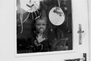 Child on window with pacifier