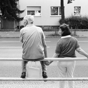 A father waiting for the bus with his daughter, holding her hand because of her physical and mental limitations as she does not see things in three dimensions like others.