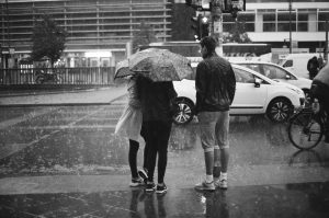 Two girls under an umbrella and a boy in the pouring rain.