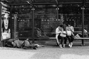 Homeless man sleeping next to Berlin tourists. Germany. 2016 © Linus Ma. all rights reserved / www.linusma.com