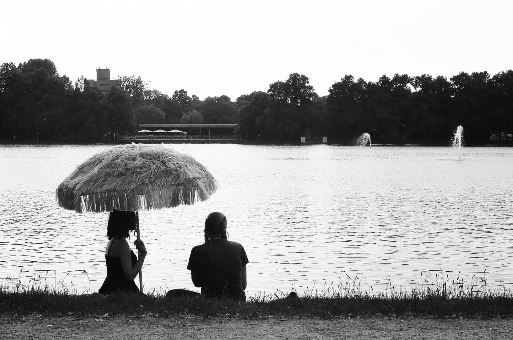 Two friends sitting under an hawaiian umbrella. Köln. Germany. 2016 © Linus Ma. all rights reserved / www.linusma.com